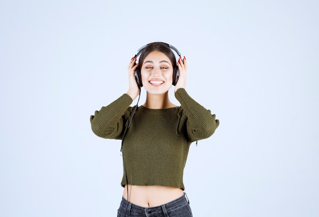 Portret van expressief jong meisje, luisteren naar muziek op witte achtergrond.
