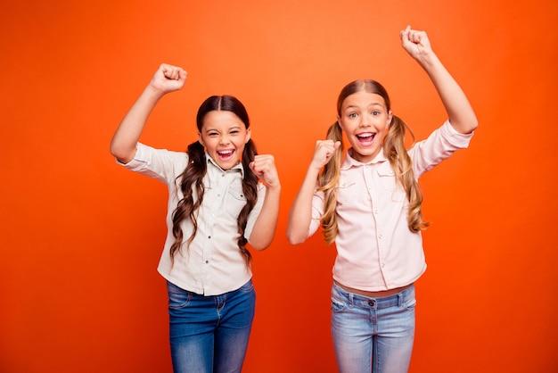 Portret van extatisch twee kinderen meisje wint competitie voel gek schreeuw ja, steek vuisten op, draag moderne outfit geïsoleerd over oranje kleur achtergrond