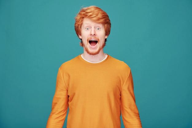 Portret van extatische emotionele roodharige man met kraal vrolijk schreeuwen op blauw