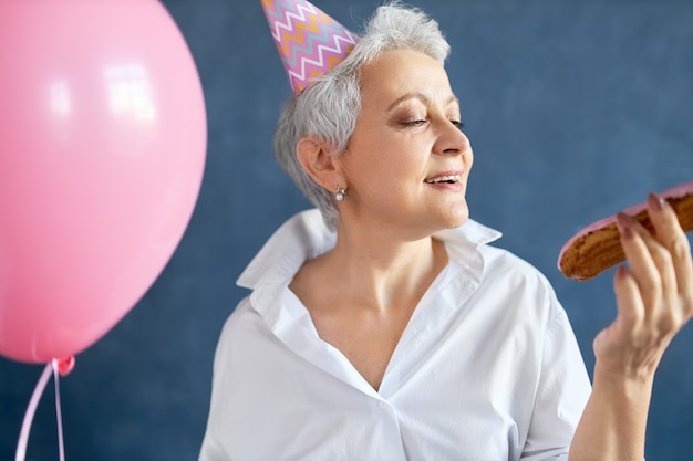 Portret van extatische gelukkige gepensioneerde dame in stijlvol wit overhemd en kegel hoed dansen op muziek op verjaardagsfeestje, met roze heliumballon.