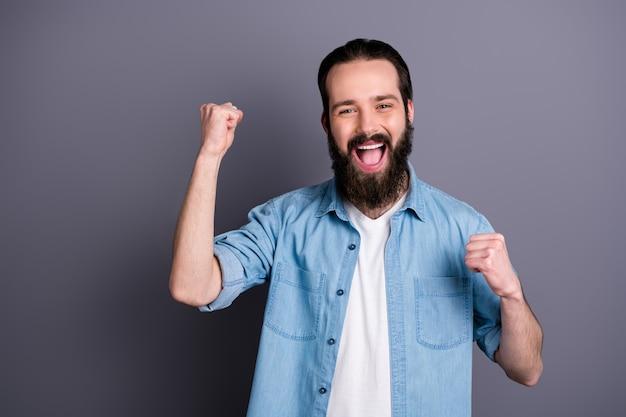 Portret van extatische kerel wint loterij jackpot, steekt vuisten op, schreeuw ja, draag goede kleding die over grijze kleurenmuur wordt geïsoleerd