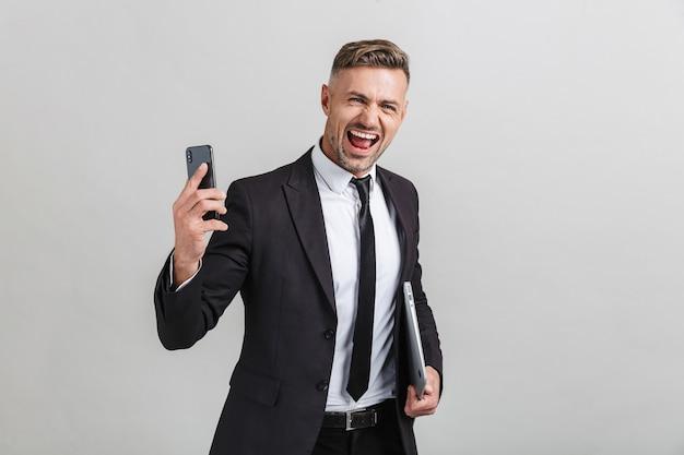 Portret van extatische volwassen zakenman in kantoorpak met smartphone en laptop terwijl hij geïsoleerd staat