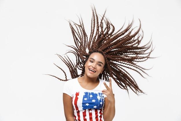 Portret van extatische vrouw die plezier heeft en haar afro-kapsel schudt terwijl ze geïsoleerd tegen een witte muur staat