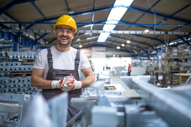 Portret van fabrieksarbeider in beschermende uitrusting in productiehal