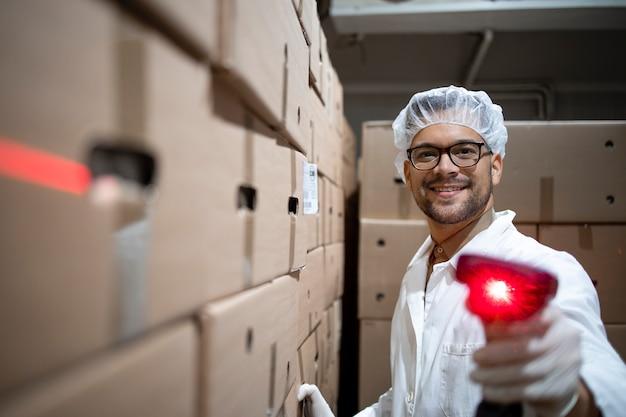Portret van fabrieksarbeider met haarnetje en hygiënische handschoenen met streepjescodescanner in voedselmagazijn.