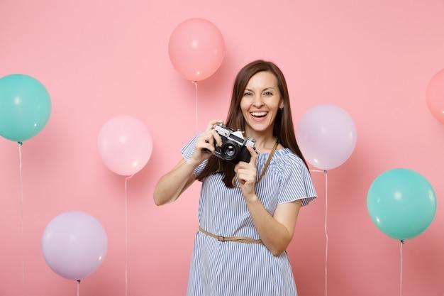 Portret van fascinerende jonge gelukkige vrouw in blauwe jurk met retro vintage fotocamera op felroze achtergrond met kleurrijke luchtballonnen. verjaardag vakantie partij mensen oprechte emoties concept.