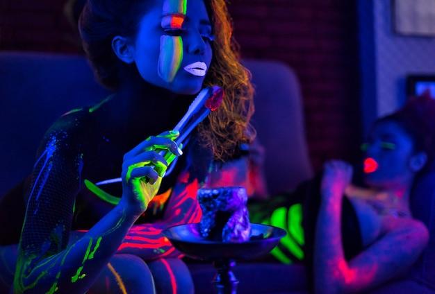 Portret van fashion model vrouw in uv neon licht met fluorescerende gloeiende body art make-up. ze blaast houtskool uit een waterpijp. rustig donker beeld. soft focus afbeelding.