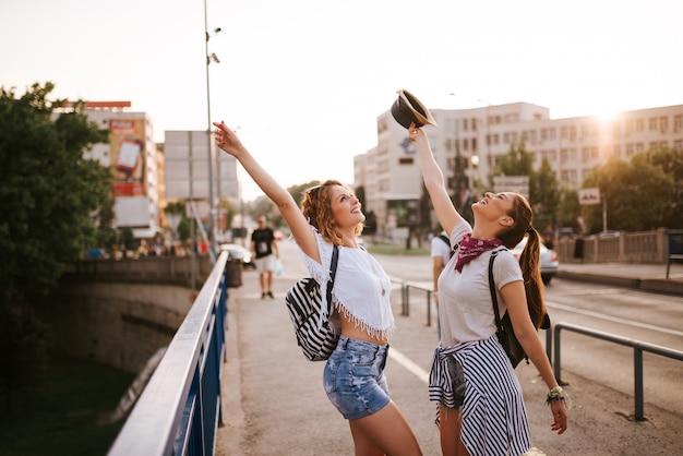 Portret van feestelijke vrolijke meisjes met opgeheven armen dansen op de brug in de stad.