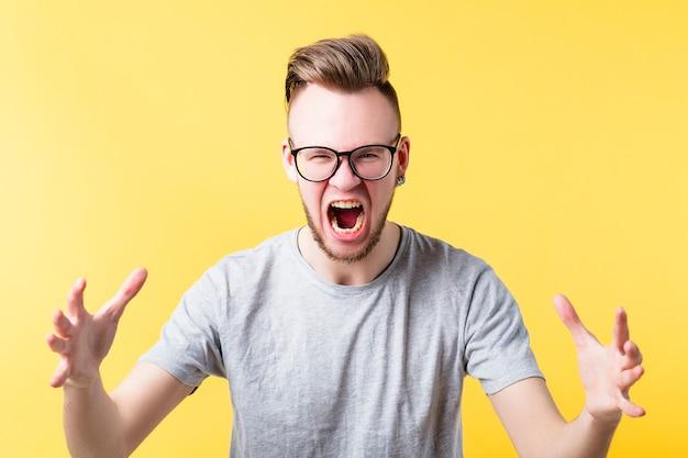 Portret van felle hipster man op gele achtergrond. schreeuwende jonge emotionele man in glazen. geïrriteerde gezichtsuitdrukking.