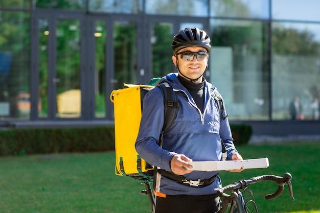 Portret van fietskoerier met gele zak en fiets