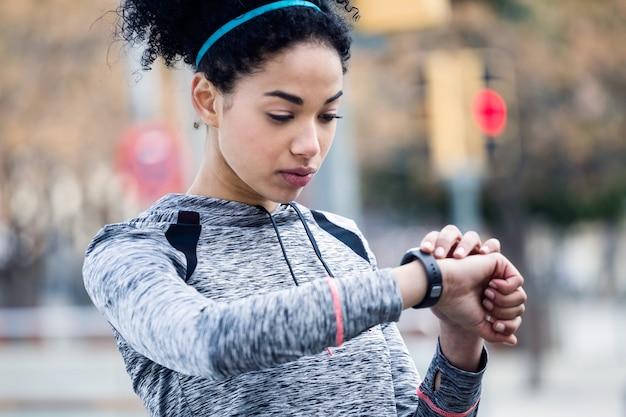 Portret van fit en sportieve jonge vrouw ontspannen na het sporten in het park.