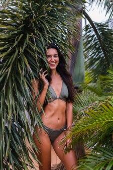 Portret van fit gelooide slanke vrouw in het groene kleine bikini poseren met tropische bladeren