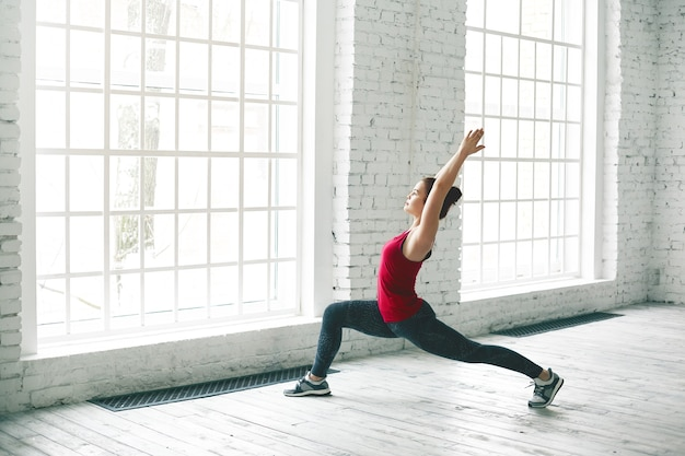 Portret van fit jonge europese vrouw in hardloopschoenen het beoefenen van verschillende yoga asana's bij lichte ruime gymzaal, halve pose of hoge lunge doen. energie, flexibiliteit, kracht en krachtconcept
