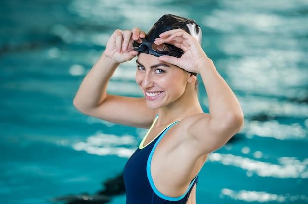 Portret van fit jonge vrouw, gekleed in badmuts en bril bij het zwembad