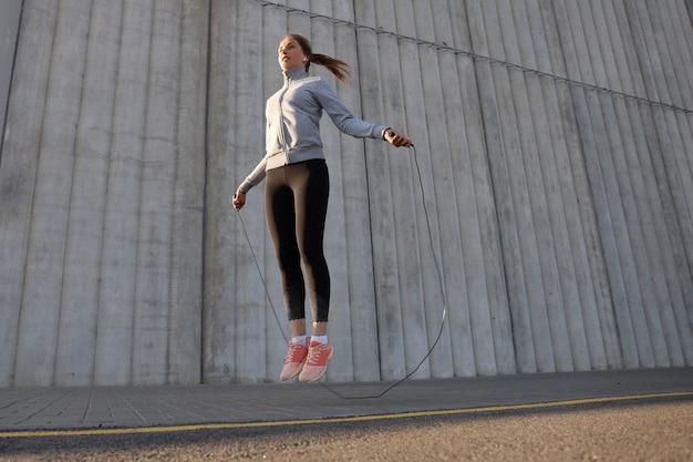 Portret van fit jonge vrouw met springtouw buitenshuis. fitness vrouw doet training overslaan buiten op zonsopgang of zonsondergang.