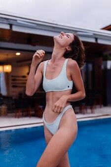 Portret van fit slanke jonge blanke vrouw in blauwe bikini buiten villa bij zwembad op regenachtige dag