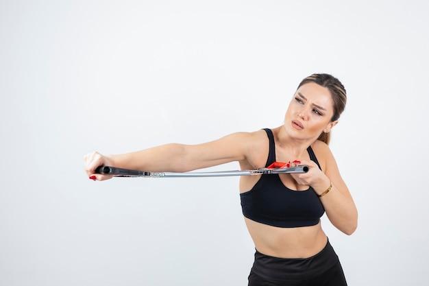 Portret van fit vrouw trainen met gym tool.