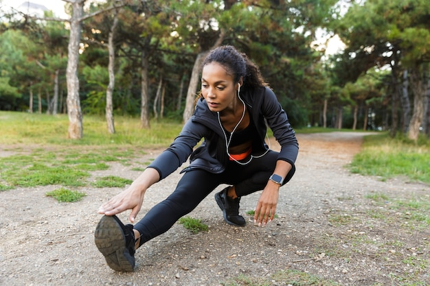 Portret van fitness afrikaanse amerikaanse vrouw 20s die zwart trainingspak dragen die oefeningen doen, en haar benen strekken in groen park