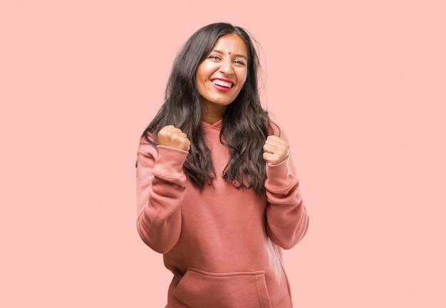 Portret van fitness jonge indiase vrouw erg blij en opgewonden, het verhogen van de armen, het vieren van een overwinning of succes