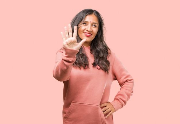Portret van fitness jonge indiase vrouw met nummer vijf, symbool van het tellen, concept van wiskunde, zelfverzekerd en vrolijk