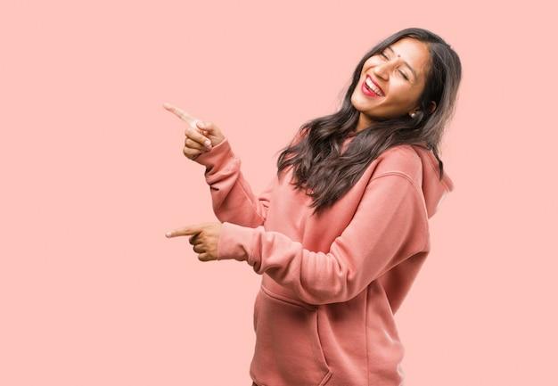 Portret van fitness jonge indiase vrouw wijzend naar de kant, glimlachend verrast iets presenteert, natuurlijke en casual