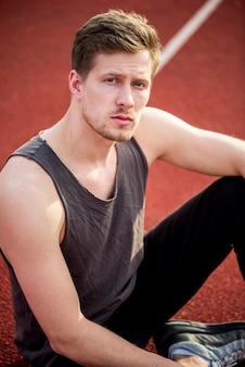 Portret van fitness jonge man zittend op track veld