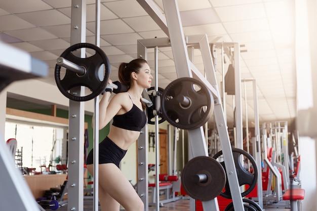 Portret van fitness jonge vrouw opleiding bij gymnastiek met halters op haar schouders. gespierde jonge vrouwelijke atleet op sportschool, dame in zwarte top en korte met paardenstaart.