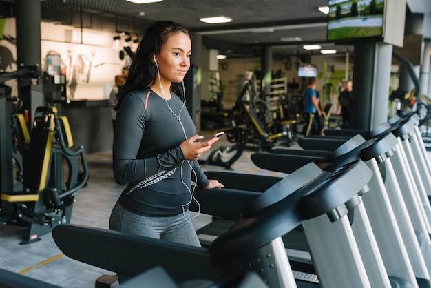 Portret van fitness vrouw draait op loopband in sportschool luisteren naar muziek. oefeningsconcept. fitheid en gezonde levensstijl.
