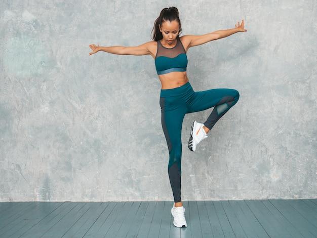 Portret van fitness vrouw in sportkleding op zoek zelfverzekerd. jonge vrouw sportkleding dragen. mooi model met perfect gebruinde lichaam. vrouwelijke springen in de studio in de buurt van grijze muur