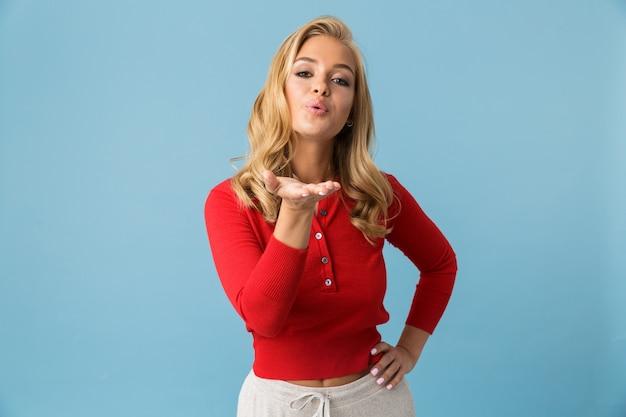 Portret van flirtende blonde vrouwen20s die rood overhemd dragen dat luchtkus geeft, die over blauwe muur wordt geïsoleerd