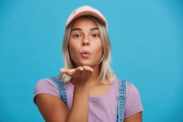 Portret van flirterige aantrekkelijke blonde jonge vrouw draagt roze pet en violet t-shirt ziet er speels uit en verzendt luchtkus geïsoleerd over blauwe muur