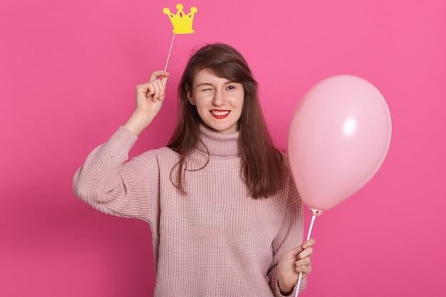 Portret van flirterige aantrekkelijke donkerharige knipogende vrouw met roze ballon