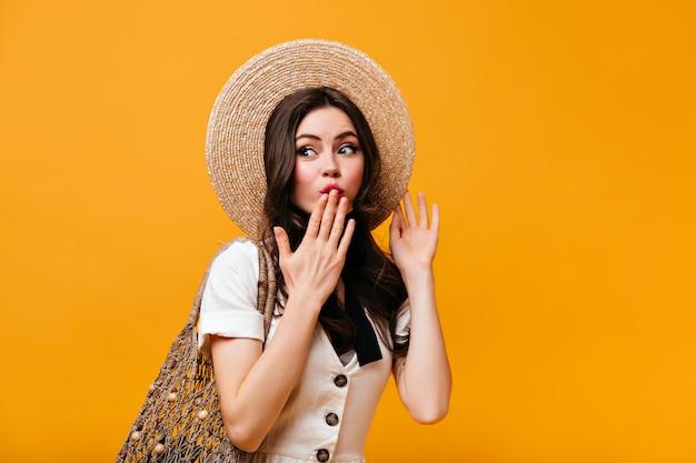 Portret van flirterige vrouw in strooien hoed en wit t-shirt voor haar mond met hand en boodschappentas op oranje achtergrond te houden.