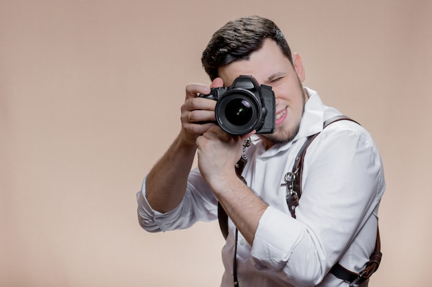 Portret van fotograaf fotograferen met digitale camera op bruine achtergrond close-up.