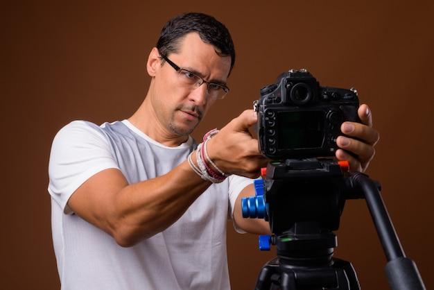 Portret van fotograaf man op zoek camera op statief