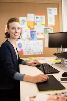 Portret van fotoredacteur die op kantoor werkt