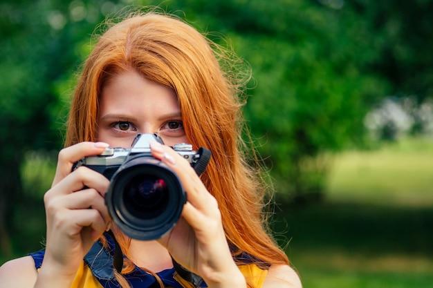 Portret van fotosessie professionele mooie jonge gember roodharige ierse meisje in een gele jurk gefotografeerd in het zomerpark. fotograaf in fotoshoot met een grote camera en een coole lens.