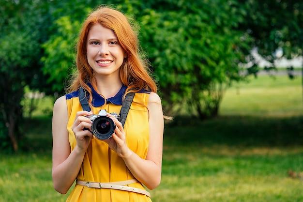 Portret van fotosessie professionele mooie jonge gember roodharige ierse meisje in een gele jurk gefotografeerd in het zomerpark. fotograaf in fotoshoot met een grote camera en een gave lens