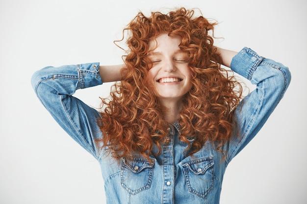 Portret van foxy mooi meisje wat betreft haar dat met gesloten ogen over witte baackground glimlacht.