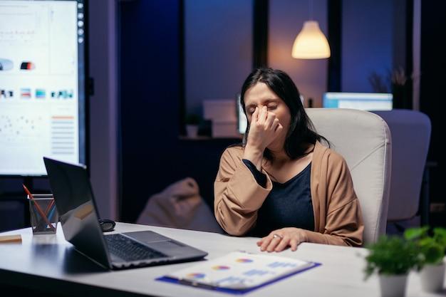 Portret van freelancer met hoofdpijn die zich overwerkt voelt vanwege de deadline van de baan. werknemer valt in slaap terwijl hij 's avonds laat alleen op kantoor werkt voor een belangrijk bedrijfsproject.