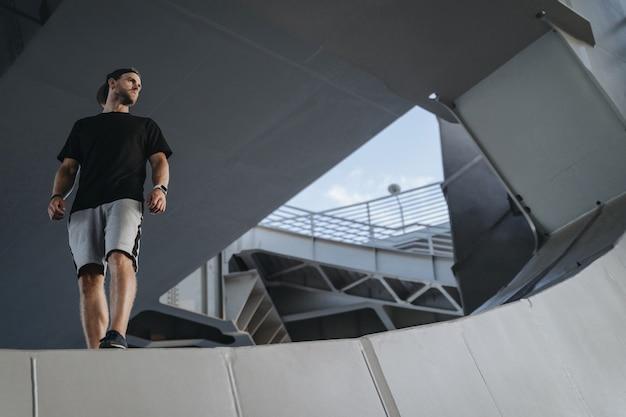 Portret van freerunning atleet staande op de metalen randconstructie. op zoek naar een plek voor uw advertentie