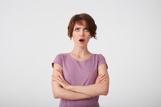 Portret van fronsende kortharige dame in leeg t-shirt, beledigd opgezocht, ziet er verdrietig en ongelukkig uit, staat op witte achtergrond met gekruiste armen.