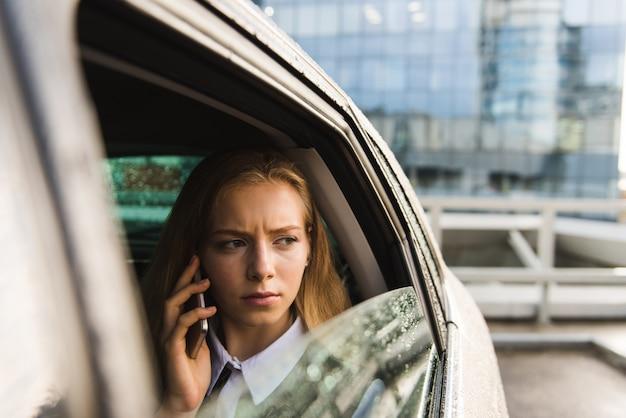 Portret van fronsvrouw in auto met mobiel