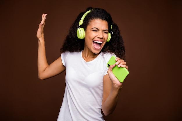 Portret van funky afro-amerikaanse jeugd stel je voor dat ze een rockconcert uitvoert, een liedje zingt, gebruik een smartphone-microfoon, luister naar muziek op een groene draadloze headset, draag een wit t-shirt.