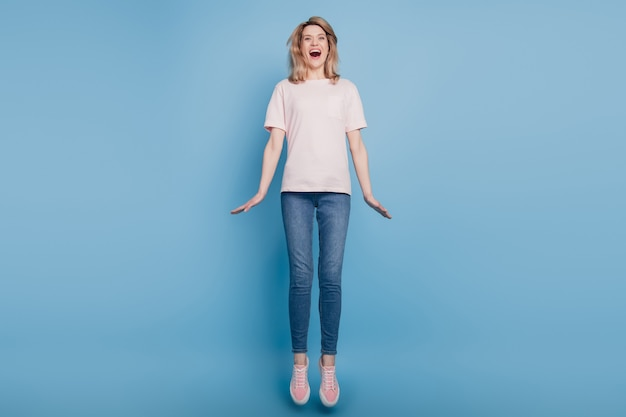 Portret van funky gekke sportieve aardige dame sprong gekke leuke open mond op blauwe achtergrond