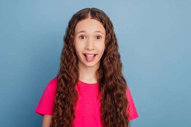 Portret van funky grappig opgewonden gek meisje kijkt camera op blauwe achtergrond