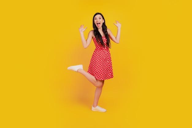Portret van funky opgewonden verbaasde dame schreeuw verheug je op gestippelde rode mini-jurk sneakers op gele achtergrond