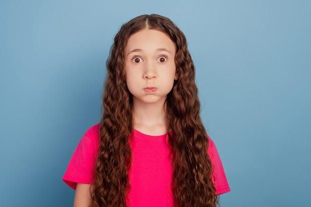 Portret van funky schattig lief mooi meisje blaast wangen op blauwe achtergrond