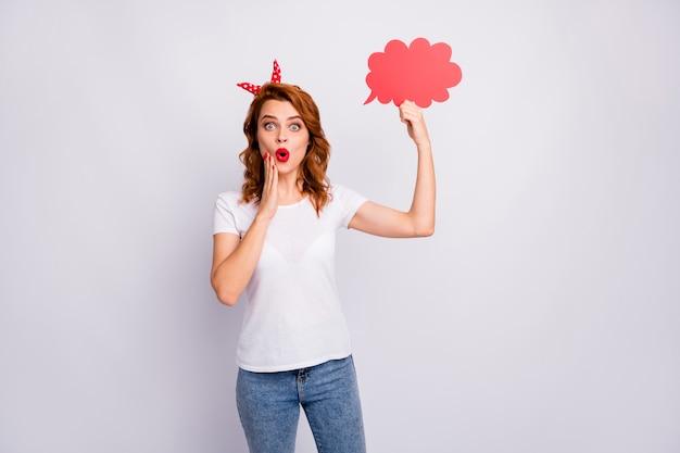 Portret van funky verbaasd meisje houdt rode papieren kaart tekstballon denk gedachten onder de indruk schreeuw wow omg draag goed kijken kleding geïsoleerd over witte kleur muur