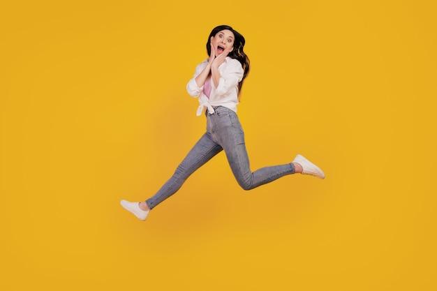 Portret van funky verbaasd meisje springt op wangen op gele achtergrond